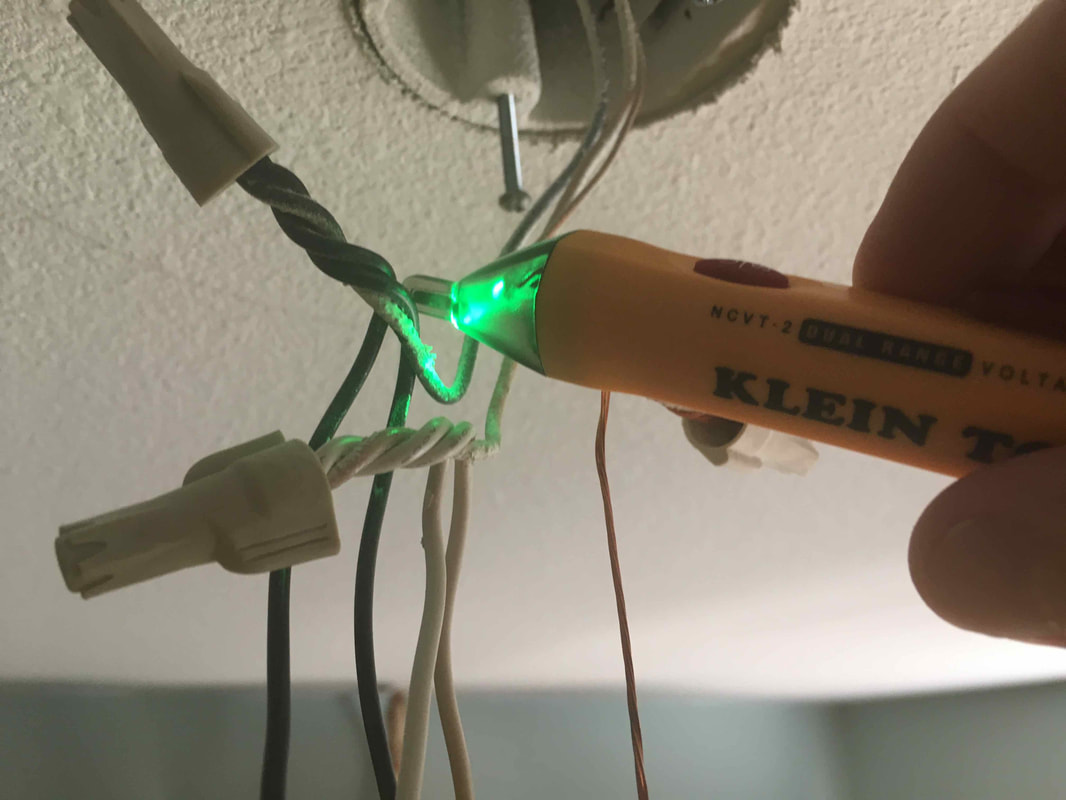 Using a non contact tester on an electrical wire.
