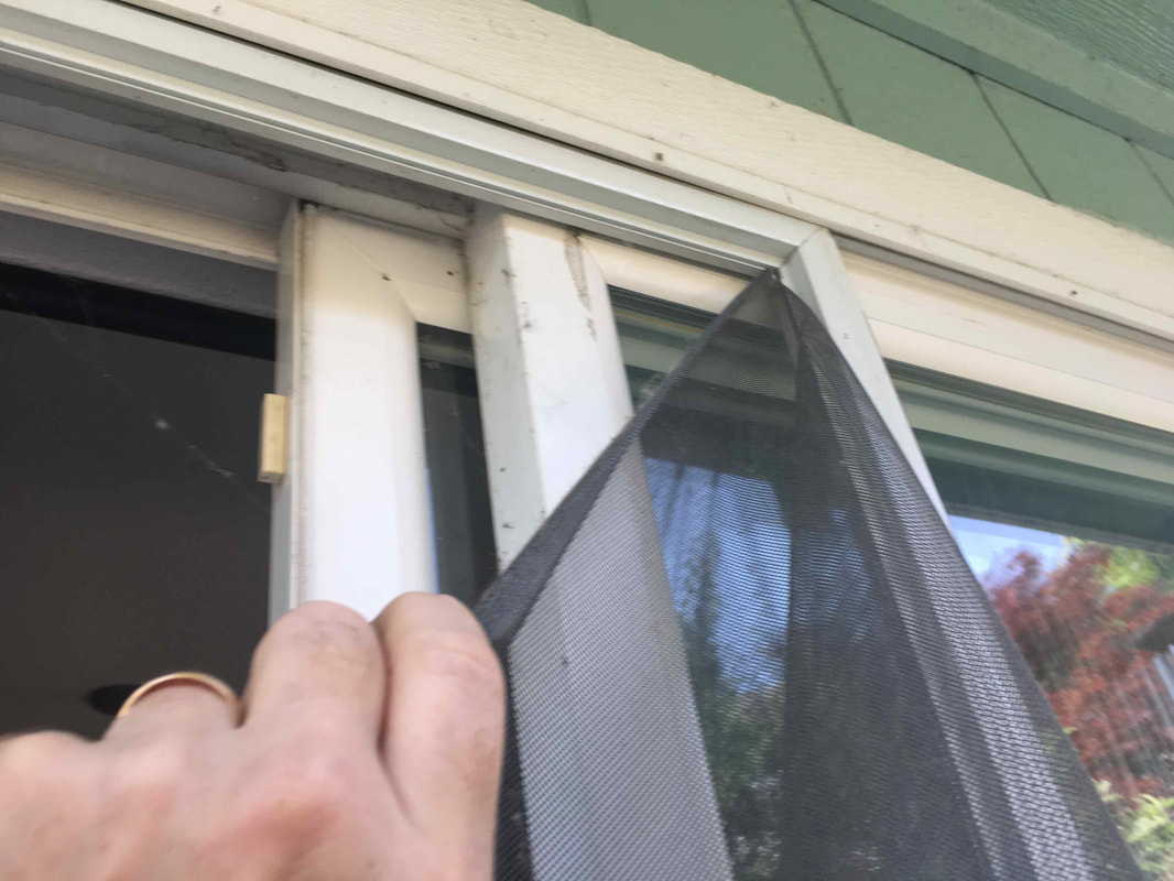 Removing the damaged screen from a screen door.