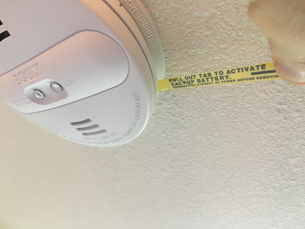 Pulling the activation strip on a smoke alarm.