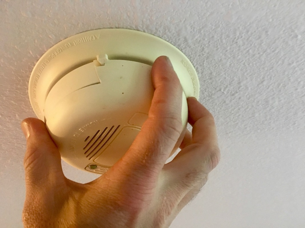 Hand removing a smoke alarm body from the baseplate.